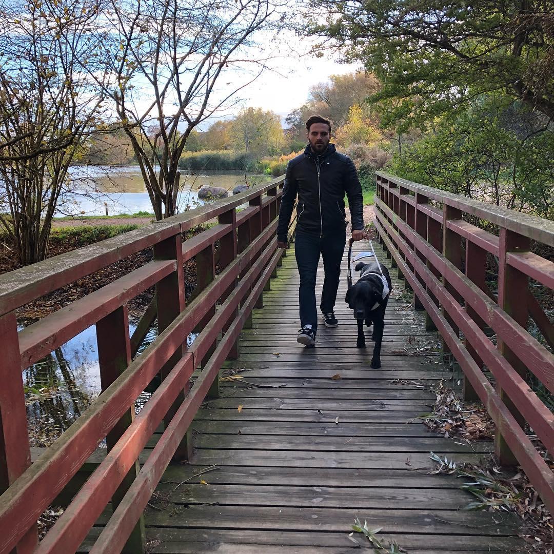 Bild på Fatmir som är ute och går med sin ledarhund på en träbro. En damm i bakgrunden