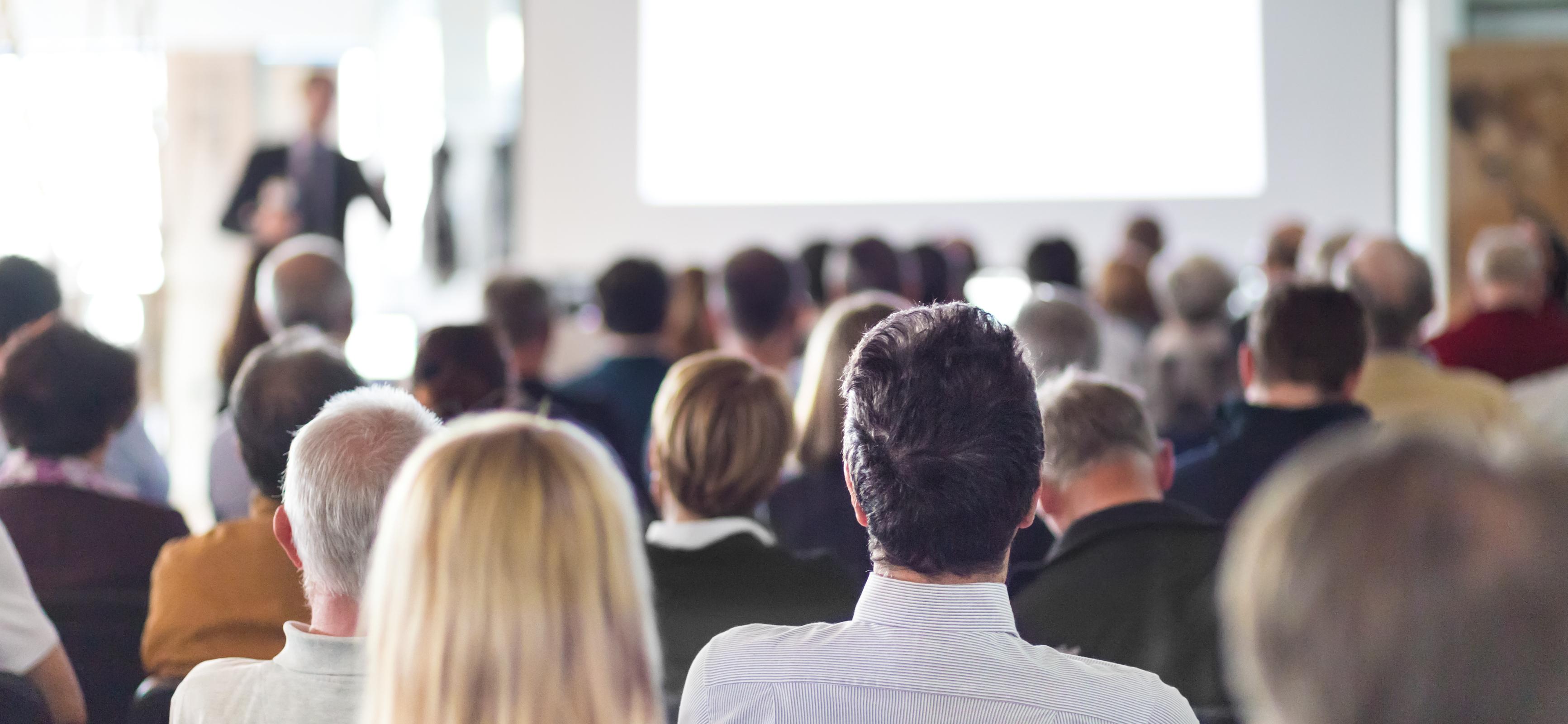 Bild på en föreläsning med flertalet människor i publiken
