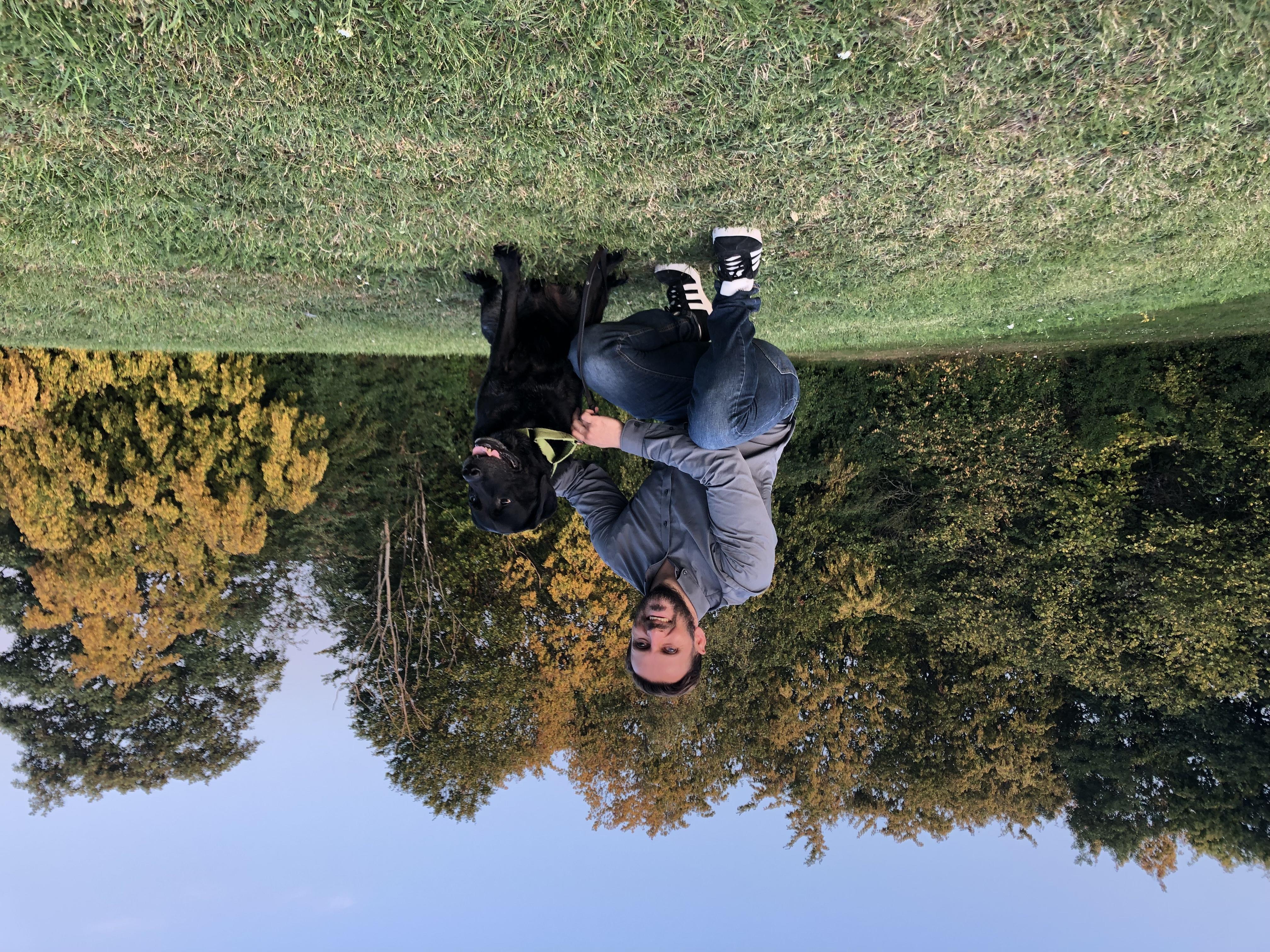 Fatmir och ledarhunden Gibson sitter bredvid varandra på en gräsbevuxen kulle. I bakgrunden finns höga träd och blå himmel.