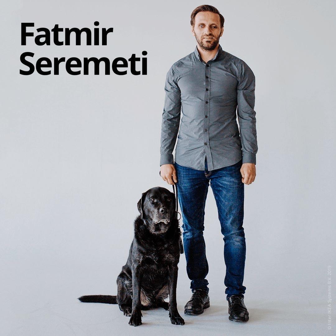 Fatmir Seremeti står på ett trägolv med sin ledarhund Gibson bredvid sig. Fatmir bär en mörkgrå skjorta och blå jeans och svarta finskor.