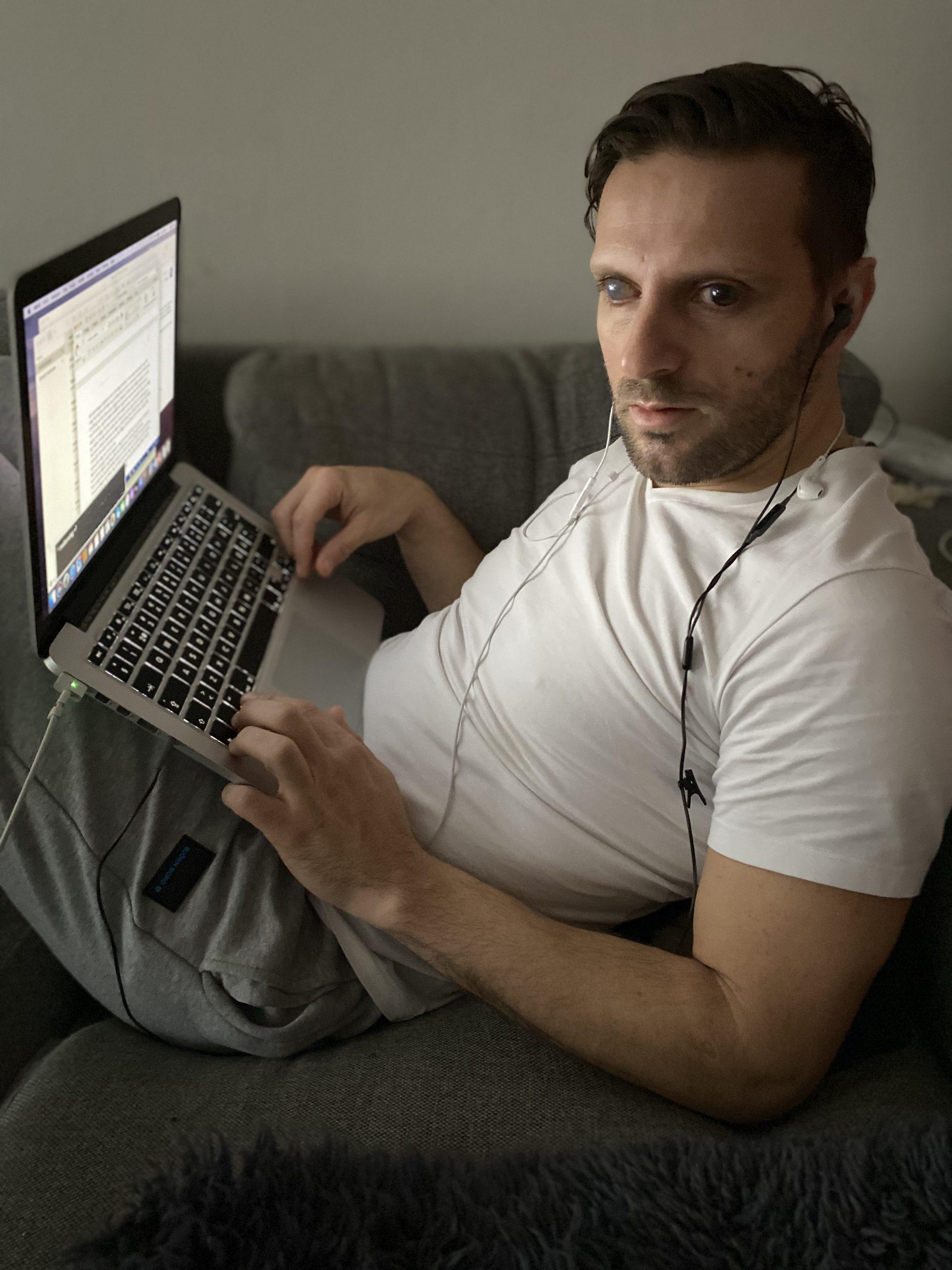 Fatmir Seremeti sitter med datorn i knät på soffan.