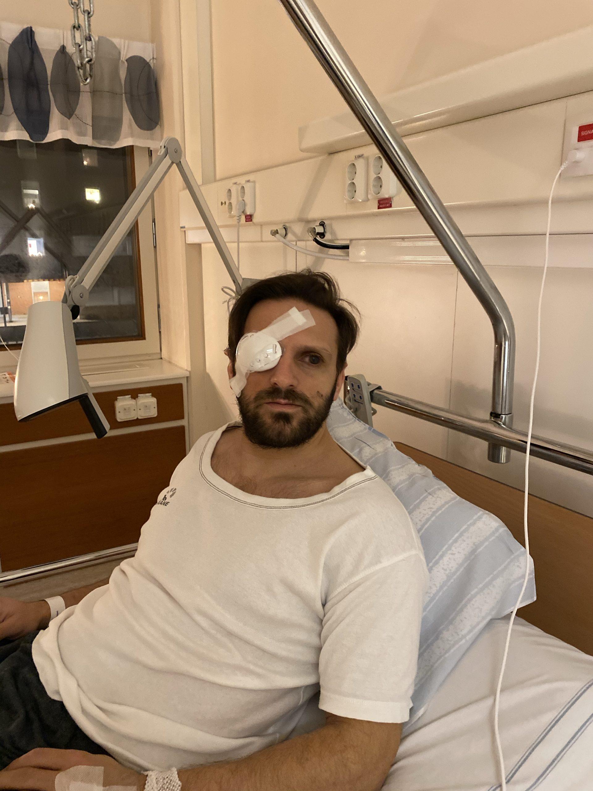 Fatmir Seremeti i en sjukhussäng i regionens sjukhuskläder på sig. Fatmir har ett bandage och plastkåpa för högerögat.