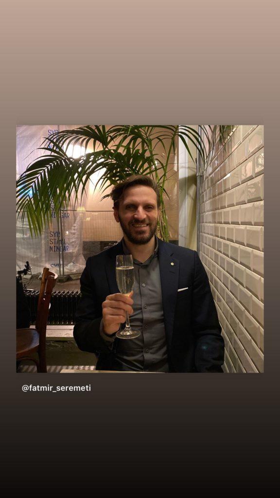 Fatmir Seremeti sitter ner med ett glas champagne i handen. Han bär en mörkblå kavaj och en stålgrå skjorta. Han ler mot kameran.