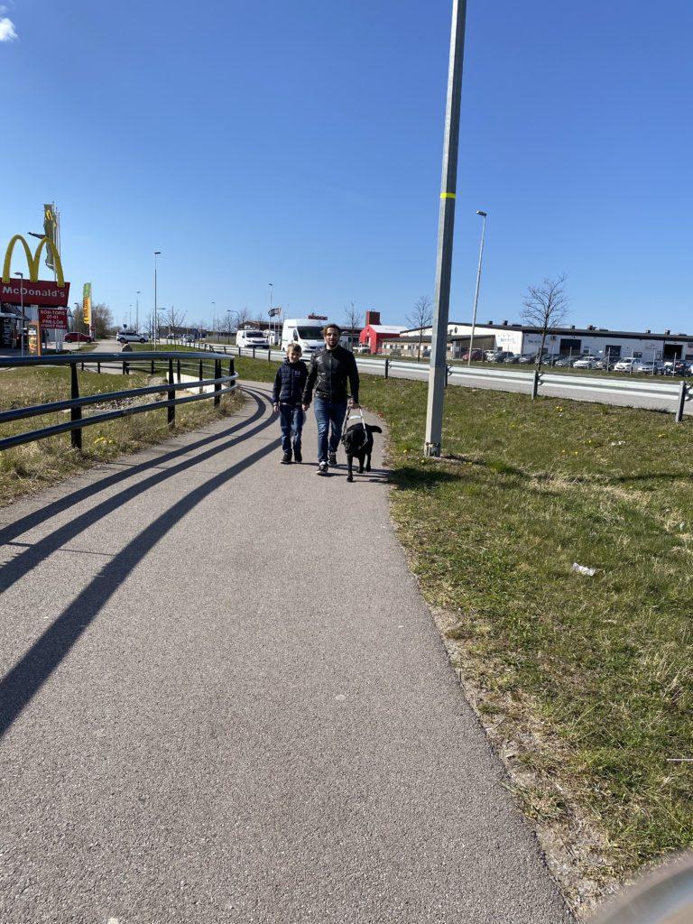 Fatmir Seremeti går på en gång och cykelbana med sin ledarhund Gibson till vänster om sig och sin son Adrian till höger.